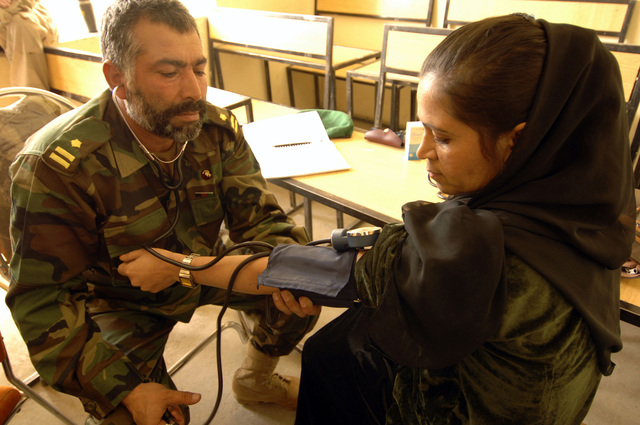 An ANA (Afghan National Army) Medic (left) takes the blood pressure of an Afghan woman during a MEDCAP (medical operations) at the Shahed Sayed Padsha School, Kandahar City, Afghanistan, 15 February 2006. (U.S. Army PHOTO by SPC. Leslie Angulo) (Released)