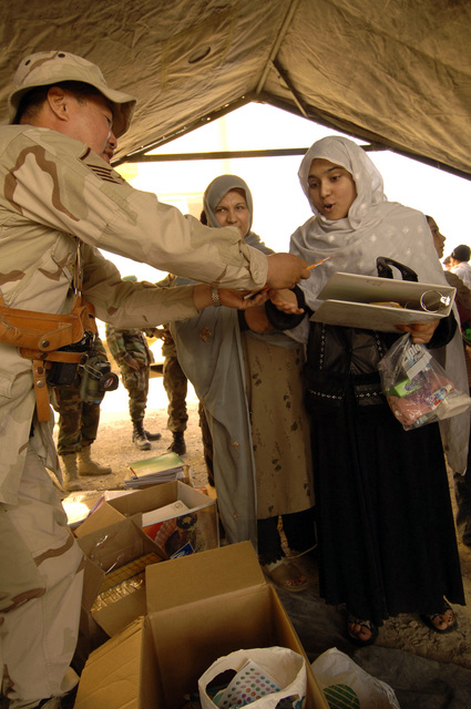 U.S. Air Force SSgt Rowen Pangamban (left) issues various school supplies to a Afghan student during a MEDCAP (medical operations) at the Shahed Sayed Padsha School, Kandahar City, Afghanistan, 15 February 2006. (U.S. Army PHOTO by SPC. Leslie Angulo) (Released)