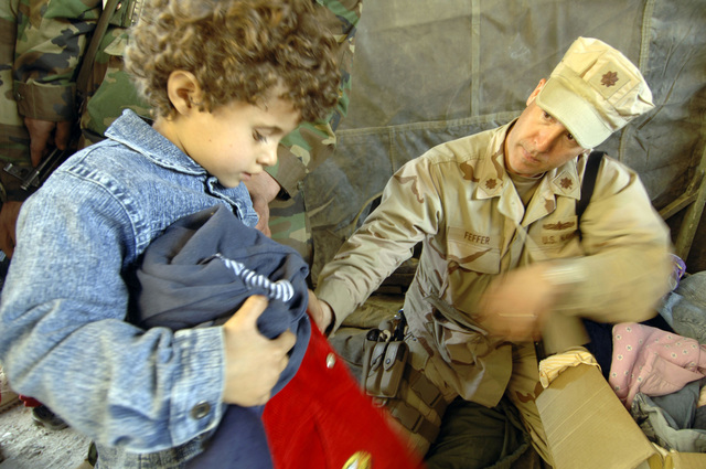 U.S. Navy LCDR Mark Feffer (right) distributes clothes to an Afghan Girl during a MEDCAP (medical operations) at the Shahed Sayed Padsha School, Kandahar City, Afghanistan, 15 February 2006. (U.S. Army PHOTO by SPC. Leslie Angulo) (Released)