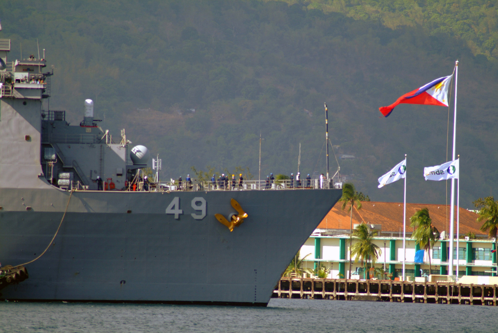 A view showing the starboard side bow of the US Navy (USN) Dock Landing Ship, USS HARPERS FERRY (LSD 49), as the ship is assisted by a tugboat while docking at Subic Bay, Philippines, after arriving to provide much needed humanitarian assistance for the victims of a devastating landslide, as part of the Forward Deployed, Amphibious Ready Group (ARG), the Navy's only forward-deployed amphibious force, out of Sasebo, Japan