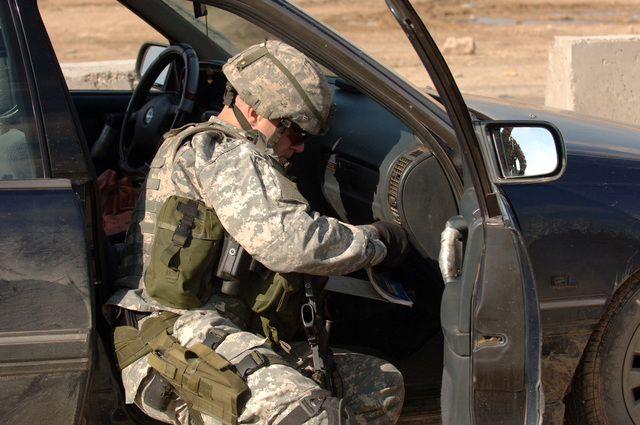 A soldier from the 1ST Battalion,17th Infantry Regiment looks through the glove box in a car at a Traffic Control Point on 18 February 2006 in Mosul,Iraq in Support of Operation Iraqi Freedom.CREDIT U.S. ARMY PHOTO: SPC Clydell Kinchen(Released)