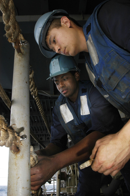US Navy (USN) SEAMAN (SN) Gavin Takata and SN Roger Lewis rig lifelines aboard the USN Aircraft Carrier USS KITTY HAWK (CV 63). Lifelines run the perimeter of the ship as a safety precaution to prevent Sailors and equipment from falling overboard