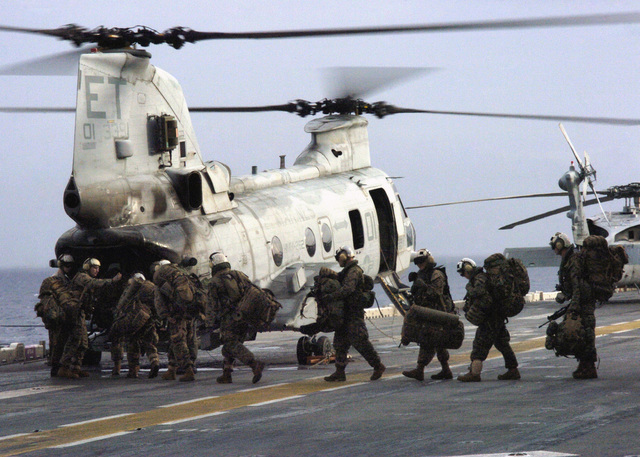 A US Marine Corps (USMC) Marines assigned to the 31st Marine Expeditionary Unit (MEU), board a CH-46E Sea Knight helicopter assigned to the Aviation Combat Element, Marine Medium Helicopter Squadron 262 (MHM-262) (Reinforced), onboard the flight deck of the USN Navy (USN) Wasp Class Amphibious Assault Ship, USS ESSEX (LHD 2), before departing to assist with humanitarian assistance and recovery efforts at Saint Bernard, Philippines, at the request of the Philippine government. This relief effort is a result of a mudslide, which devastated the town of Guinsahugon located in the southern part of the island of Leyte in the Philippines. (SUBSTANDARD)