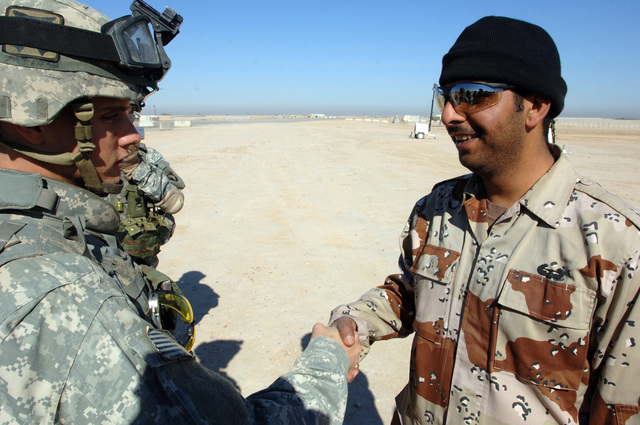 PFC Leroy Minion from B battery from 3rd Battalion, 320th Field Artillery awards an Iraqi Soldier after he completed a successful air assault mission in the area of Al Salam in Tikrit, Iraq on February 24, 2006. The raid operation was performed by coalition forces from the 101st Division and 4th Division Iraqi Army in search of weapon caches.(U.S. Army photo by SPECIALIST Teddy Wade) (Released)