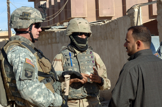 SGT. First Class Robert Leek of 1ST Platoon, C Company, 1ST Battalion, 187th Infantry Regiment, 101st Airbourne Division and his interpretor speak to a local man during a dismounted patrol through As Saliniyah, Iraq on February 24, 2006.  Patrols such as this help to show an active presence in the community and enforce local rules. (US Army photo by SPC. Charles W. Gill)(Released)