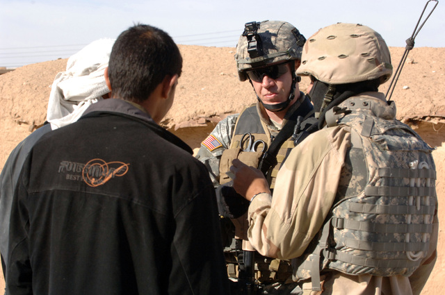 SGT. First Class Robert Leek of 1ST Platoon, C Company, 1ST Battalion, 187th Infantry Regiment, 101st Airbourne Division and his interpretor speak to locals during a dismounted patrol through As Saliniyah, Iraq on February 24, 2006.  Patrols such as this help to show an active presence in the community and enforce local rules. (US Army photo by SPC. Charles W. Gill)(Released)