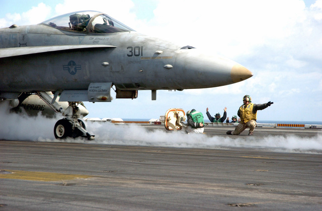 "A US Navy (USN) (yellow shirt) Catapult Officer gives the signal to launch as a F/A-18C Hornet aircraft assigned to the ""Valions"" of Strike Fighter Squadron 15 (VFA-15) prepares to launch from the flight deck of the USN Nimitz Class Aircraft Carrier, USS THEODORE ROOSEVELT (CVN 71). The ROOSEVELT and embarked Carrier Air Wing 8 (CVW-8) are currently on a regularly scheduled deployment conducting maritime security operations in the Mediterranean Sea"