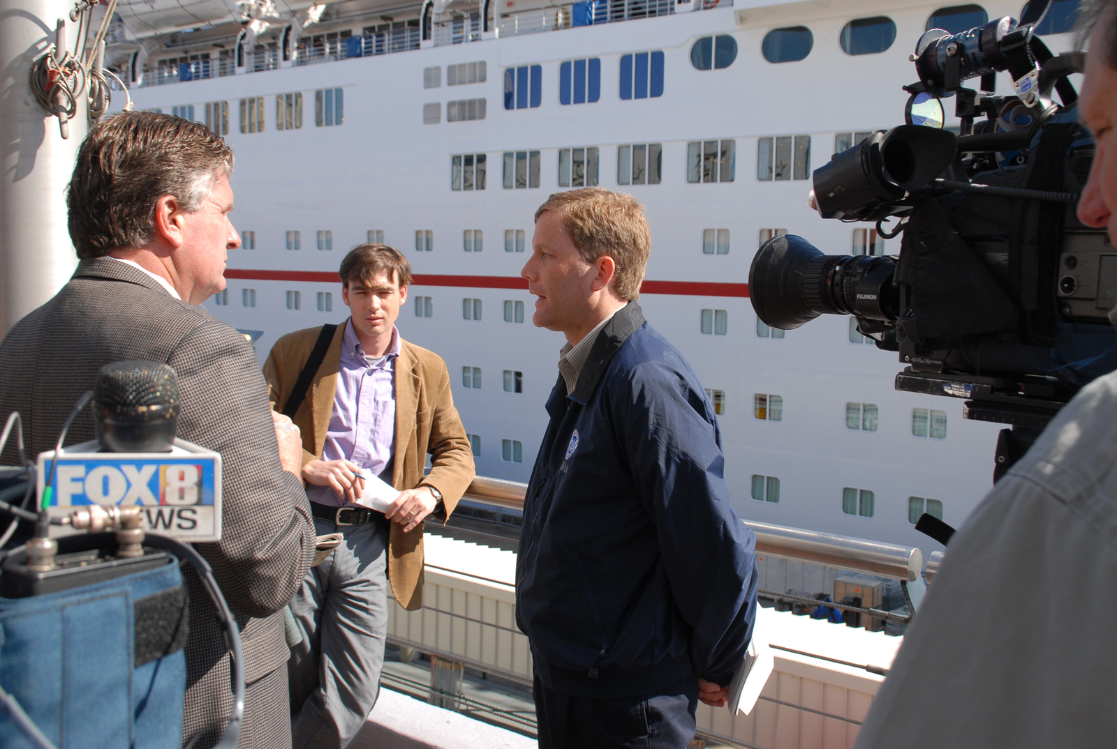 "[Hurricane Katrina] New Orleans, St. Bernard, LA, 02-27-06 -- FEMA Public Affairs Officer Dave Passey talks to reporter Rob Masson from Fox News 8 at the cruise ship ""Sensation"" about the progress of cruise ship residents moving into land based housing.  FEMA is helping victims living on the cruise ships find long term housing before the Ships contract expires March 1st and the ship sets sail.  Marvin Nauman/FEMA photo"