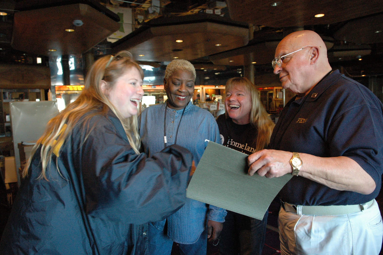[Hurricane Katrina] Pascagoula, Miss., February 27, 2006 -- FEMA  officials (L-R) Traci Skinner, Betty C. Lewis, Pattie Silven and Rico Borrazo share a light moment on the cruise ship Holiday as they await the disembarkment of the final resident aboard ship.  The Holiday served as temporary housing for Mississippi residents displaced from their homes by Hurricane Katrina.  Mark Wolfe/FEMA