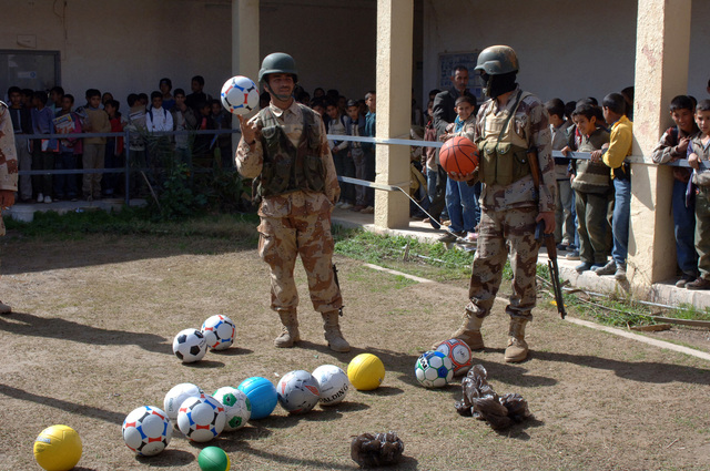 Soldiers of the 2nd Brigade, 4th Iraqi Army Division and Iraqi Police show goodwill toward the community by visiting local schools and handing out toys and school supplies in Bayji, Iraq on Feb. 28, 2006. Gestures such as this are conducted to build a relationship between the Iraqi Army and the local population.  (U.S. Army photo by SPC. Charles W. Gill) (Released)