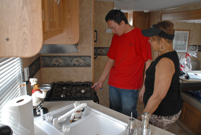 """[Hurricane Katrina] New Orleans, LA, 3-1-06 -- Trailer service engineer Thomas Tran shows Brenda Green the operation of her gas stove in her new FEMA travel Trailer that she just moved into. Brenda just moved off the cruse ship Ecstasy into the new FEMA trailer park at """"Wisner Play Ground"""" and is still looking at her long term housing options.  Marvin Nauman/FEMA photo"""