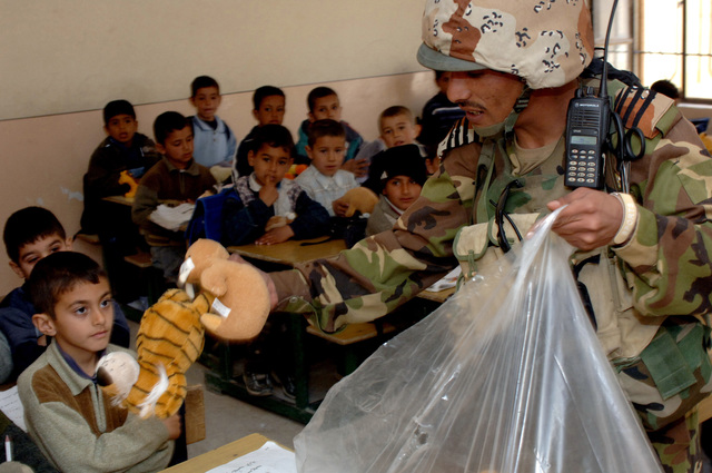 Soldiers of the 2nd Brigade, 4th Iraqi Army Division show goodwill toward the community by visiting local schools and handing out toys and school supplies in Siniah, Iraq on March 1, 2006. An Iraqi Soldier passes out toys at the Al Faaraby primary school for boys. Gestures such as this are helping to building a better relationship between the Iraqi Army and local communities. (U.S. Army photo by SPC. Charles W. Gill) (Released)