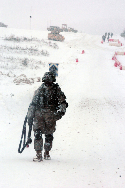 Convoy NCOIC STAFF. SGT. Terrance Sizemore from A Company, 299th Forward Support Battalion, part of Task Force 1-26th Infantry, 2nd Brigade Combat Team, 1ST Infantry Division, marches to the scene of a jackknifed fueler part of the convoy to take supplies to the Forward Operations Base Summerall as a part of the Mission Rehearsal Exercise Noble Shepherd in Hohenfels, Germany on March 2, 2006. (U.S. Army photo by STAFF SGT. Ricky Melton) (Released)