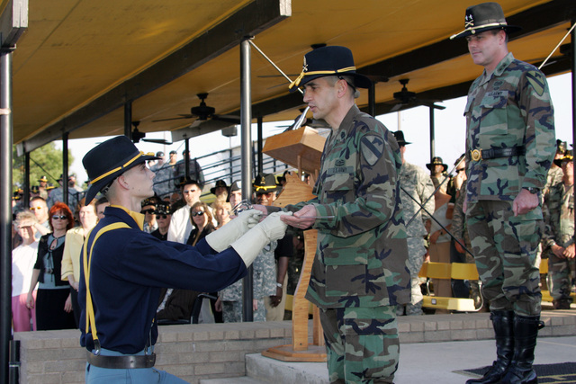 U.S. Army Command SGT. MAJ. Philip F. Johndrow, 1ST Cavalry Division, assumes responsibility as the First Team's top Non-Commissioned Officer (NCO).   During the ceremony, MAJ. GEN. Joseph F. Fil (right), First Cavalry Division Commander, stands by as a member of the First Cavalry Division's Honor Guard, SPC. Isaiah P. Hagan presents a sword to Command SGT. MAJ. Johndrow, on Guideon Field, at Fort Hood, Texas. (U.S. Army PHOTO by John Byerly, CIV) (Released)