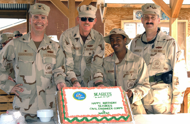 At Camp Moreell, Kuwait (KWT) (left to right), US Navy (USN) 22nd Naval Construction Force (NCR) Captain (CAPT) Eric Odderstol with the Naval Mobile Construction Battalion 22 (NMCB-22), Assistant Officer-in-Charge (OC) MASTER CHIEF PETTY Officer (MCPO) Craig Nelson, NMCB-7 representative Mister Kevin Beckworth and 1ST Naval Construction Division (NCD) Deputy Commander, Commodore (CMDR) Albert Garcia III, celebrate the Seabees' 64th birthday with a cake
