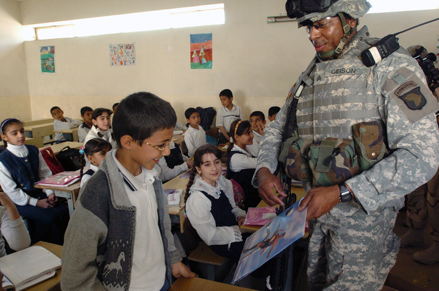 US Army (USA) Sergeant (SGT) Kendrick Gibson, assigned to Hammerhead Headquarters Battery 4-320th Field Artillery Regiment, 506th Regimental Combat Team, 101st Airborne Division (AASLT), hands out school supplies, donated by children from Medora Elementary School in Jefferson County, Kentucky (KY), to a class of Iraqi school children in Baghdad, Iraq (IRQ)
