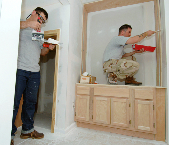 In Gulfport, Mississippi (MS), US Navy (USN) Aviation Structural Mechanic 3rd Class (AM3) Joshua Corl (left) and Machinist's Mate 2nd Class (MM2) David Gayton spackle the kitchen walls in a storm damaged home, while preparing the interior for repainting. Twenty-three Sailors assigned to the Nimitz-class aircraft carrier USS HARRY S. TRUMAN (CVN 75) are part of a community relations team, working side-by-side with civilian volunteers from around the world through Camp Hope