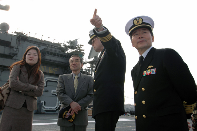The US Navy (USN) Commanding Officer (CO) of the USN Aircraft Carrier USS KITTY HAWK (CV 63), Captain (CAPT) Ed McNamee, escorts Japanese Maritime Self Defense Force (JMSDF) Vice Admiral (VADM) Tsutomo Tamura, president of the Japan Maritime Self Defense Force STAFF College and renowned Japanese sword maker and Yoshi Yoshihara, around the flight deck