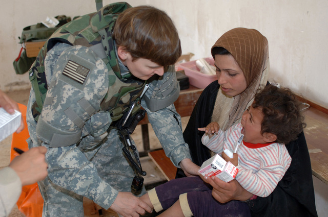 On March 8, 2006, U.S. Soldiers from Charlie, 2-22 Infantry on Military Police Liberty and Iraqi soldiers from 3rd Brigade, 6th Iraqi Army Division located on Forward Operating Base Constitution held a MEDCAP for the people of Al Jaddi Village. The purpose of the operation was to assist with humanity needs of local villagers and develop targetable intelligence. The MEDCAP was held at Al Jeel Al Arahi Primary School (Mix). Iraqi soldiers provided outter seurity. A women gets her daugther hand and leg checked out.(U.S. Army photo by STAFF SGT. Kevin L. Moses Sr.) (Released)