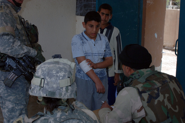 On March 8, 2006, U.S. Soldiers from Charlie, 2-22 Infantry on Military Police Liberty and Iraqi soldiers from 3rd Brigade, 6th Iraqi Army Division located on Forward Operating Base Constitution held a MEDCAP for the people of Al Jaddi Village. The purpose of the operation was to assist with humanity needs of local villagers and develop targetable intelligence. The MEDCAP was held at Al Jeel Al Arahi Primary School (Mix). A boy explains that is arm that hurts him.(U.S. Army photo by STAFF SGT. Kevin L. Moses Sr.) (Released)