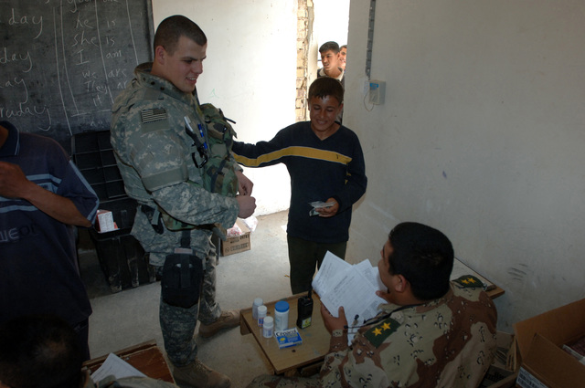 On March 8, 2006, U.S. Soldiers from Charlie, 2-22 Infantry on Military Police Liberty and Iraqi soldiers from 3rd Brigade, 6th Iraqi Army Division located on Forward Operating Base Constitution held a MEDCAP for the people of Al Jaddi Village. The purpose of the operation was to assist with humanity needs of local villagers and develop targetable intelligence. The MEDCAP was held at Al Jeel Al Arahi Primary School (Mix). An Iraqi Army LT. talks to a patient.(U.S. Army photo by STAFF SGT. Kevin L. Moses Sr.) (Released)
