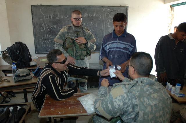 On March 8, 2006, U.S. Soldiers from Charlie, 2-22 Infantry on Military Police Liberty and Iraqi soldiers from 3rd Brigade, 6th Iraqi Army Division located on Forward Operating Base Constitution held a MEDCAP for the people of Al Jaddi Village. The purpose of the operation was to assist with humanity needs of local villagers and develop targetable intelligence. The MEDCAP was held at Al Jeel Al Arahi Primary School (Mix). U.S. Army CAPT. Swenness prescribes and gives a boy medicine.(U.S. Army photo by STAFF SGT. Kevin L. Moses Sr.) (Released)