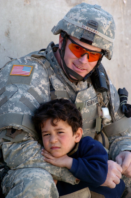US Army (USA) Corporal (CPL) James Reinhard, Vipers Task Force (TF), Headquarters/Headquarters Detachment (HHD), 519th Military Police (MP) Company (MP Co), comforts 5-year old Okmed outside of an Iraqi Police (IP) station in Baghdad, Baghdad Province, Iraq (IRQ), while taking a break from training and assisting IP officers during Operation IRAQI FREEDOM