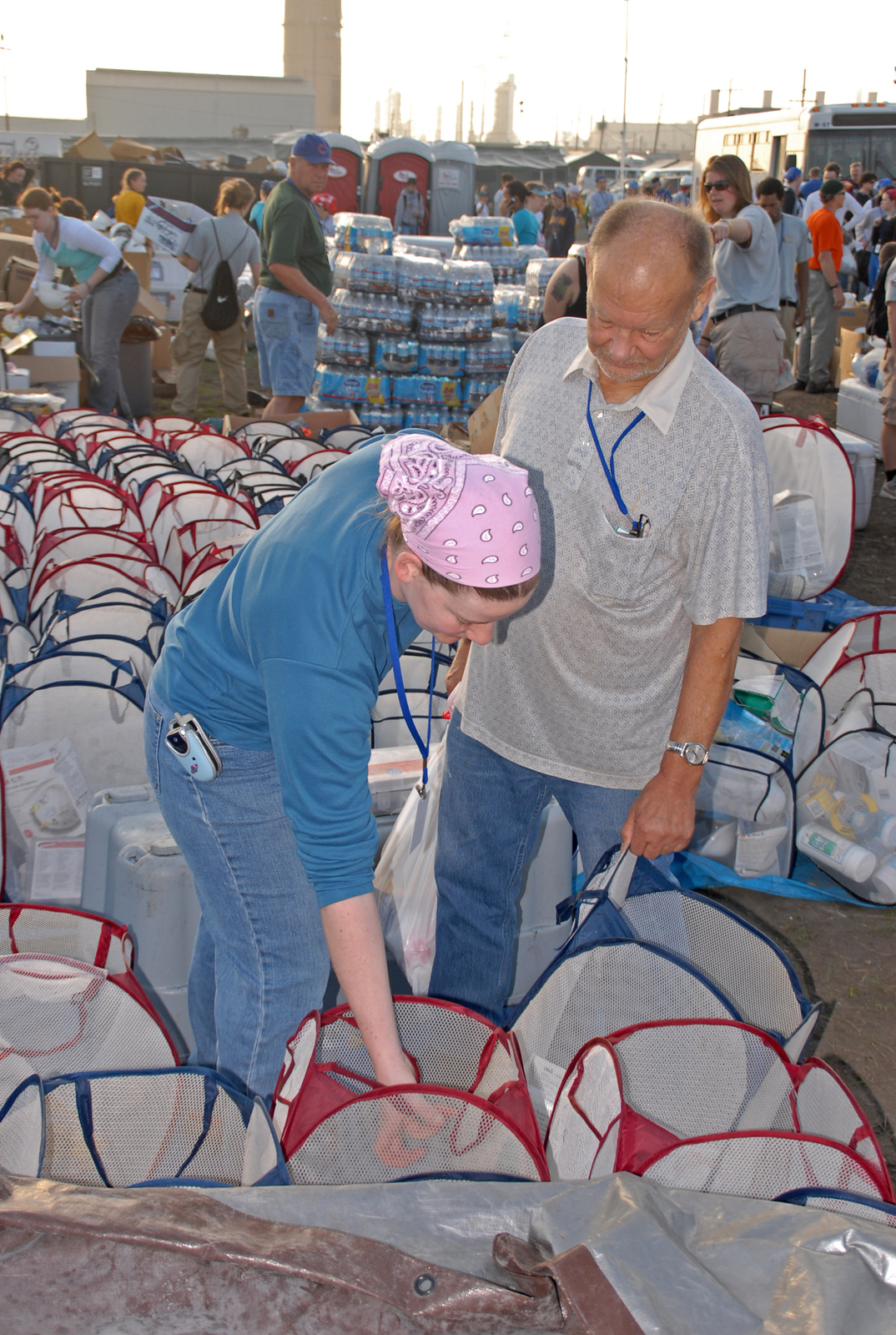 """[Hurricane Katrina] New Orleans, LA, 3-13-06 -- Volunteer Team Leader Earl Romans of """"Earls Alaskans"""" helps volunteer Team Leader Casey Schoen from the University of Alaska at Fairbanks and Rotaract pick up her protective equipment at a FEMA Base Camp.  College students from around the country are in New Orleans helping with clean up during spring break. FEMA is housing as many of the College Student volunteers as possible in four base camps in and around New Orleans.  These base camps are being expanded to accommodate more volunteers.  Marvin Nauman/FEMA photo"""