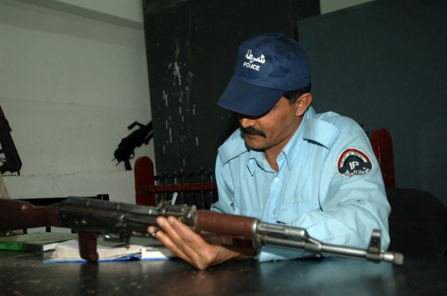 An Iraqi police officer reviews the serIraqi Armyl numbers of weapons at the Kadhimya Police Station in Baghdad, Iraq, March 15, 2006.  (U.S. Army photo by STAFF SGT. Kevin L. Mosses Sr.) (Released)