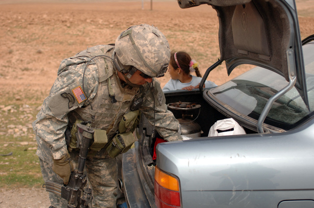 U.S. Army SGT. 1ST Class Jason Hall from the 172nd Stryker Brigade Combat Team searches a trunk during a Flash Traffic Control Point on March 15, 2006 in Mosul, Iraq in Support of Operation Iraqi Freedom. (U.S. Army photo by SPC. Clydell Kinchen) (Released)