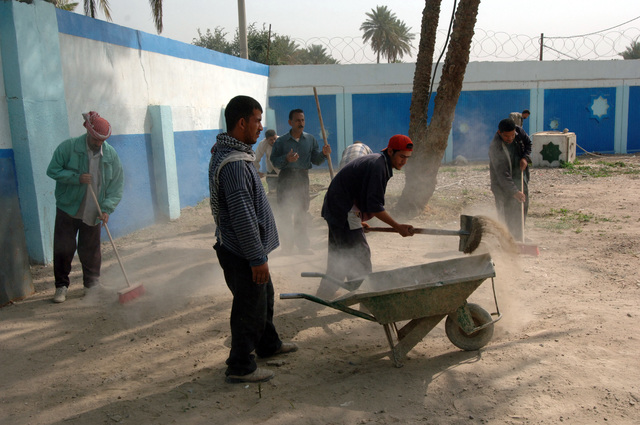 Workers remove trash from the Kadhimya Police Station in Baghdad, Iraq, March 15, 2006.  The station once held a large number of wrecked vehicles and trash.  (U.S. Army photo by STAFF SGT. Kevin L. Mosses Sr.) (Released)