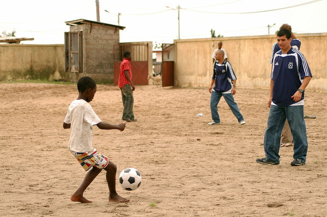 A Gabonese schoolboy from the Matanda Elementary School kicks a soccer ball to US Navy (USN) Boatswain's Mate Second Class (BM2) German Rengifomata, during a Community Relations (COMREL) project. BM2 Rengifomata is assigned aboard the USN Submarine Tender, USS EMORY S. LAND (AS 39). The LAND is currently inport at Port Gentil, Gabon conducting various COMREL projects with host nationals