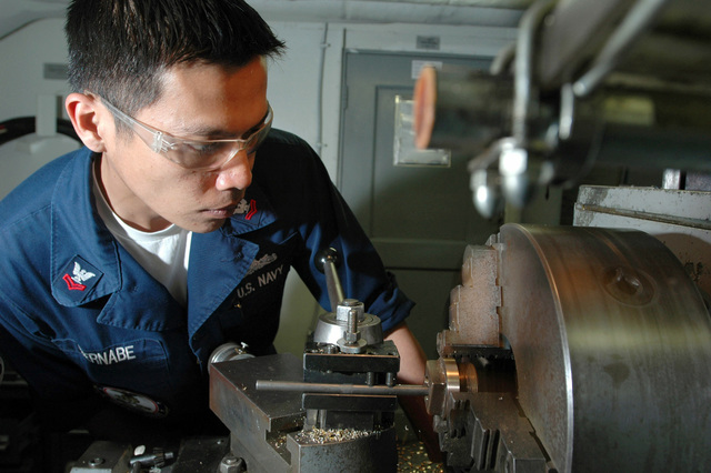Onboard the US Navy (USN) Nimitz Class, Aircraft Carrier USS JOHN C. STENNIS (CVN 74), Machinery Repairman Second Class (MR2) Emanuel Bernabe, prepares to cut threads into a brass plug. The STENNIS is currently underway in the Pacific Ocean conducting carrier qualifications