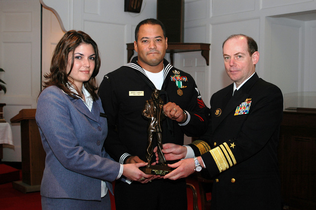 The Atlantic Fleet Sea Sailor of the Year award winner, US Navy (USN) Aviation Boatswain's Mate 1ST Class (BM1) Alfred Stansberry and his wife Tammie are presented the Lone Sailor Statuette by Vice Admiral (VADM) Kevin J. Cosgriff. The Sailor of the Year award recognizes the outstanding sailors who selflessly give themselves to the Navy and their communities with a well-rounded sense of purpose, in Norfolk, Virginia (VA)