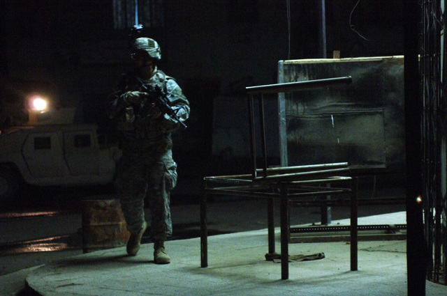 A U.S. Army Soldier from 3rd Platoon, Bravo Company, 1ST Battalion, 187th Infantry Regiment, 101st Airbourne Division provides security down on the street while fellow Soldiers search a hotel in Bayji, Iraq on March 20, 2006 for suspected insurgents and possible explosive devices.   (U.S. Army photo by SPC. Charles W. Gill) (Released)