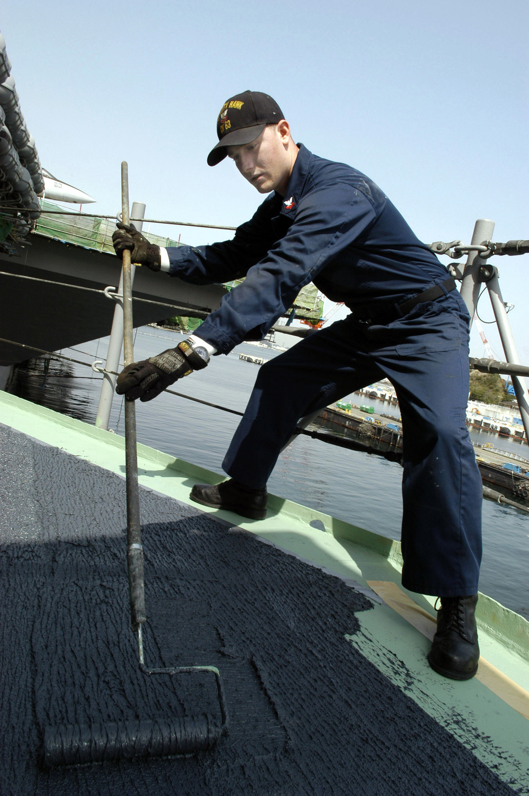 Onboard the flight deck of the US Navy (USN) Aircraft Carrier, USS KITTY HAWK (CV 63), Fire Control Technician Second Class (FT2) Justin Bogges, applies non-skid paint to the deck supporting a Rolling Airframe Missile (RAM) mount. The KITTY HAWK is currently in port at Yokosuka, Japan, conducting repairs during a restricted availability period