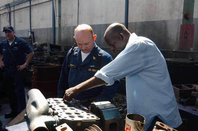 Onboard the US Navy (USN) L.Y. Spear Class Submarine Tender, USS EMORY S. LAND (AS 39), Engineman SENIOR CHIEF (ENCS) Robert Hewitt, examines an engine-block in need of repairs with a Congolese translator during a repair training evolution. The LAND is currently in port at Pointe Noire, Congo (CGO), conducting repair training evolutions and Community Relations projects with host nation nationals
