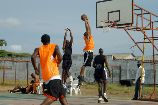 US Navy (USN) Hospital Corpman Third Class (HM3) Jonathan Scott of the USN USS EMORY S. LAND (AS 39) basketball team shoots a 10-foot jump shot over a defender from the Congo basketball team during their basketball game with the Congo International Team while on their Gulf of Guinea Deployment, Pointe Norte