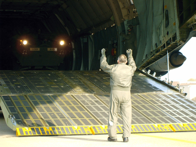 A member of a Tennesee Air National Guard crew guides one of two Stryker armored vehicles off of a C-5 Galaxy at Daegu air base in Daegu, Korea during RSOI/FOAL EAGLE, March 25, 2006. (U.S. Army photo by PFC. Nicholas A. Hernandez) (Released)