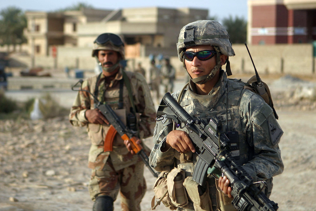 US Army (USA) SPECIALIST Fourth Class (SPC) Frank Mireles (right), Alpha Company (A Co), 1ST Battalion, 36th Infantry Regiment (1/36th), deployed with the US Marine Corps (USMC) I Marine Expeditionary Force (MEF), and an Iraqi Army (IA) Soldier (left) patrol through a neighborhood while participating in Operation MONTGOMERY in Hit, Al Anbar Province, Iraq (IRQ), during Operation IRAQI FREEDOM
