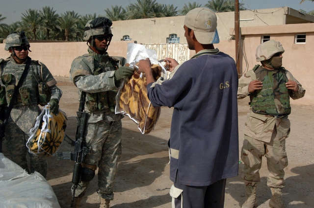 On March 26, 2006, U.S. Army Soldiers from Delta, 10th Mountain, 2nd Battalion, 22nd Infantry went to the town of Sumelat to give citizens blankets to fight the early morning chill. Soldiers wanted to let citizens know they were being though of. U.S. Army SGT. Rafael Lovell gives an Iraq man a blanket.(U.S. Army photo by STAFF SGT. Kevin L. Moses Sr.) (Released)