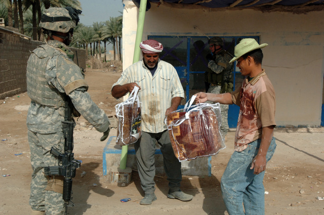 On March 26, 2006, U.S. Army Soldiers from Delta, 10th Mountain, 2nd Battalion, 22nd Infantry went to the town of Sumelat to give citizens blankets to fight the early morning chill. Soldiers wanted to let citizens know they were being though of. U.S. Army SGT. Rafael Lovell hands out blankets to local citizens.(U.S. Army photo by STAFF SGT. Kevin L. Moses Sr.) (Released)