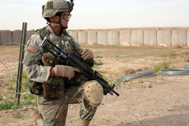 U.S. Army PFC. John Parrisy, of 3rd Platoon, Charlie Company, 1ST Battalion, 187th Infantry Regiment, 101st Airborne Division, provides security as fellow Soldiers place concertina wire to bolster fortifications at an entry control point in Siniya, Iraq, March 26, 2006.  (U.S. Army photo by SPC. Charles W. Gill) (Released)