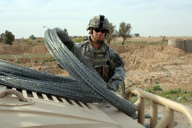 U.S. Army U.S. Army SPC. Lee Kimzey, of 3rd Platoon, Charlie Company, 1ST Battalion, 187th Infantry Regiment, 101st Airborne Division, prepares to place concertina wire to bolster fortifications at an entry control point in Siniya, Iraq, March 26, 2006.  (U.S. Army photo by SPC. Charles W. Gill) (Released)