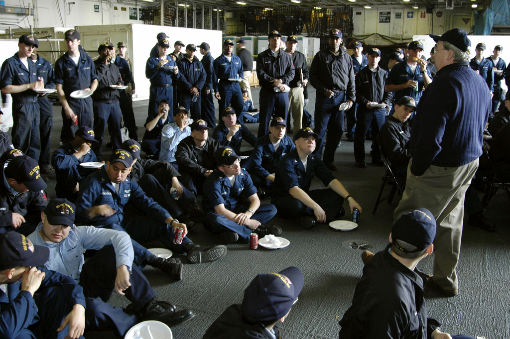 US Navy (USN) Sailors stationed aboard the Aircraft Carrier, USS KITTY HAWK (CV 63), listen as Evangelical Episcopal Priest, Father Mike Warnke (standing foreground right) delivers a motivational speech. Father Warnke is a Vietnam War Veteran and is onboard during an event sponsored by the religious ministries department while the ship is in port at Yokosuka, Japan, conducting repairs during a restricted availability period