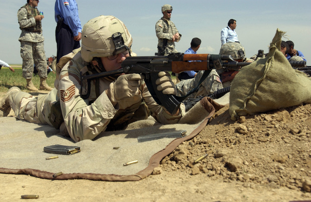 U.S. Air Force TECH. SGT. John Foster a Combat Photographer with the 1ST Combat Camera Sq., fires an AK-47 rifle during training being conducted by U.S. Army members with 4th.  Battalion, 14th. Infantry Regiment, 172nd. Infantry Brigade Combat Team, with the Iraqi Police in Khidr Ilyas, Iraq, Mar. 29, 2006. (U.S. Army photo by SPC. Ronald Wright) (Released)