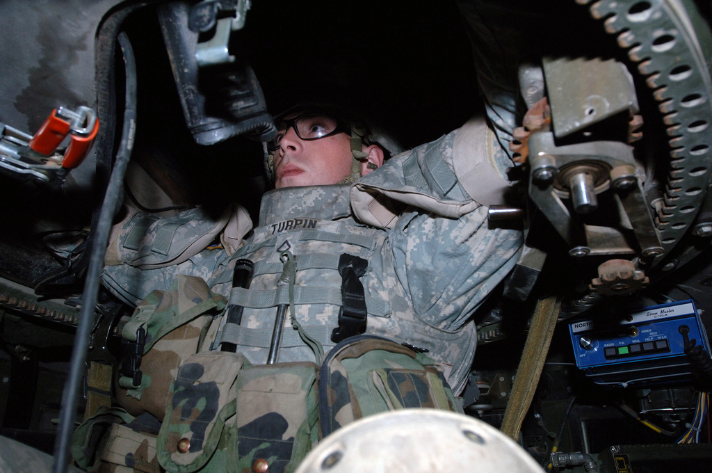 US Army (USA) Private First Class (PFC) Justin Turpin, Bravo Company (B Co), 1ST Battalion (BN), 87th Infantry Regiment (1/87th), 10th Mountain Infantry Division (ID), sits in a vehicle turret observing other USA 1/87th Soldiers setting up Traffic Control Point (TCP) Barriers on Route 49 and 50 in Baghdad, Baghdad Province, Iraq (IRQ), to assist Iraqi Police (IP) and Iraqi Army (IA) personnel in controlling the area during Operation IRAQI FREEDOM