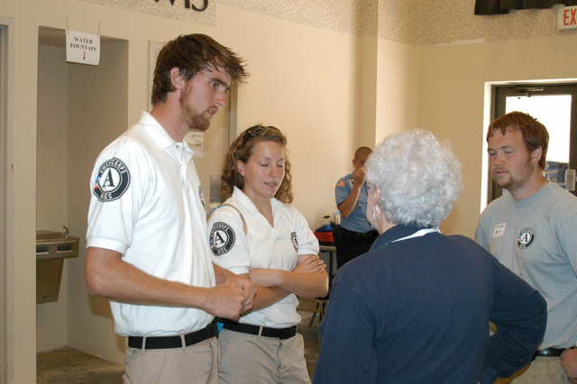 [Hurricane Katrina] Biloxi, Miss., April 1, 2006 - Americorps volunteers (L-R) Daniel Wojtowicz of Westean, Mass., Beth Crosby of Charlottesville, VA., and Cory Price, chat  with a FEMA representative while awaiting today's training at the Biloxi  Joint Field Office (JFO).  Americorps Volunteers in Biloxi are working with Habitat for Humanity and  Morrell Foundation, building housing for volunteers working in the community, with said houses to be ultimately given to those who lost their homes in Hurricane Katrina.  George Armstrong/FEMA