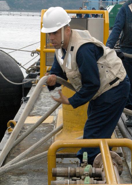 US Navy (USN) Boatswain's Mate Second Class (BN2) Angelo Miranda, assist in mooring operations as the USN Los Angeles Class Attack Submarine, USS TUCSON (SSN 770) arrives at Commander, Fleet Activities Yokosuka, Japan