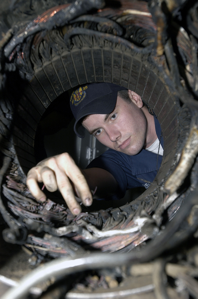 US Navy (USN) Navy PETTY Officer Third Class (PO3) Justin Russell, an Electrician stationed aboard the USN L.Y. Spear Class Submarine Tender, USS EMORY S. LAND (AS 39), inspects frayed wires in a generator that is being rewound for a local mission located in Luanda, Angola, courtesy of the ship's motor rewind shop, while in port Luanda, Angola. The LAND is the first USN ship to visit Angola is 32 years and is currently conducting repair training, AIDS awareness training, and community relations projects with host nationals